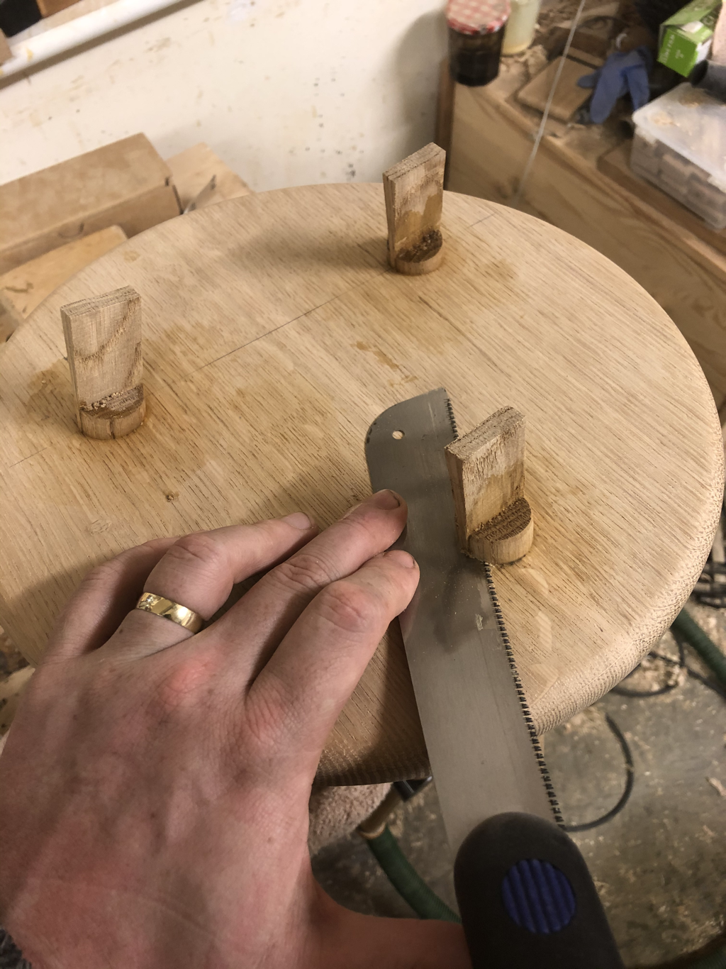 Flush cut saw being used to trim off wedges on a Stable Stool